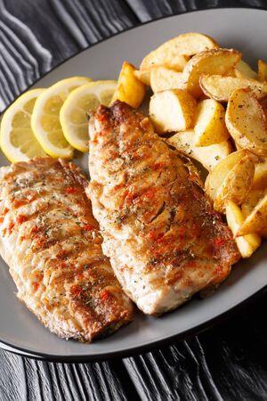 Grilled mackerel fillet with potato wedges and lemon close-up on a plate on the table. vertical