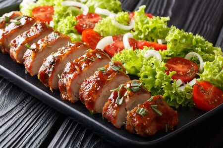 Juicy baked pork tenderloin in honey-garlic sauce served with fresh vegetables close-up on a plate on the table. horizontal