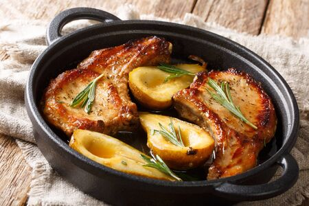 Rustic style baked pork chops with pears and rosemary in honey-garlic sauce served in a pan close-up on the table. horizontal