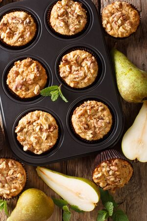 pear muffin with cinnamon and walnuts in a baking dish close-up on the table. Vertical top view from above