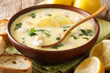 Thick aromatic Greek lemon soup with chicken and orzo paste close-up in a bowl on the table. horizontal