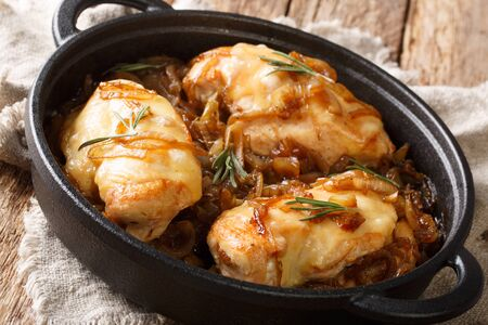 French chicken onion fillet cooked with gruyere cheese and spicy wine sauce close-up in a pan on the table. horizontal