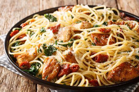 Pasta con tomates secos, pollo, parmesano y primer plano de espinacas en un plato sobre la mesa. horizontal