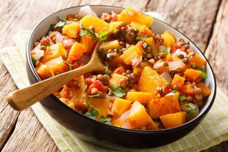 Diätetisches Ragout mit Kürbis, Linsen, Zwiebeln und Karotten in einer Schüsselnahaufnahme auf dem Tisch. horizontal
