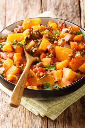 Vegetarian pumpkin curry with lentils, onions and carrots close-up in a bowl on the table. vertical