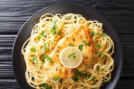 Tasty classic chicken Francaise with spaghetti in lemon wine sauce close-up on a plate on the table. Horizontal top view from above