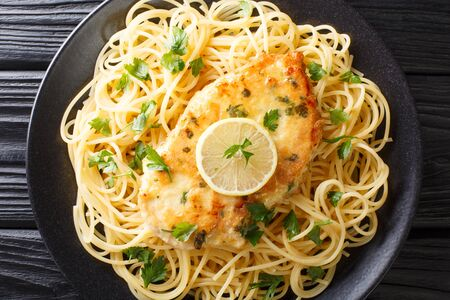 cooked chicken Francaise with spaghetti in lemon wine gravy close-up on a plate on the table. Horizontal top view from above