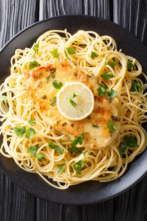 Chicken Francaise(or Chicken Francese) is an Italian-American dish served with spaghetti with lemon sauce close-up on a plate on the table.