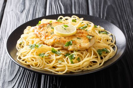 Roasted breaded chicken Francaise with a side dish of spaghetti close-up on a plate on the table. Horizontal