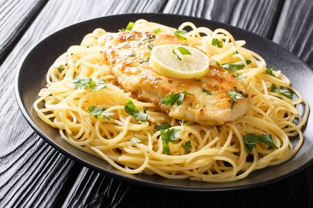 Authentic fried breaded chicken Francaise with spaghetti in lemon wine gravy close-up on a plate on the table. horizontal  Фото со стока
