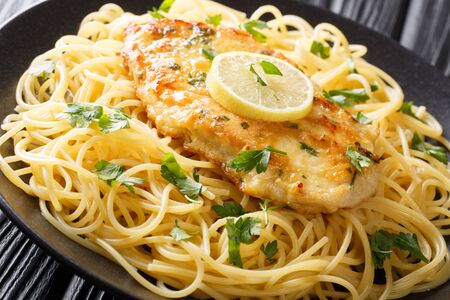 cooked chicken Francaise with spaghetti in lemon wine gravy close-up on a plate on the table. horizontal
