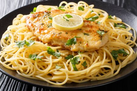 Traditional chicken Francaise with spaghetti with lemon gravy close-up on a plate on the table. horizontal