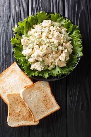Delicious chicken salad with celery, eggs and onions served with toast close-up on a plate on the table. Vertical top view from above