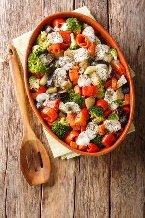 Healthy baked vegetables with mozzarella cheese close-up in a baking dish on the table. Vertical top view from above