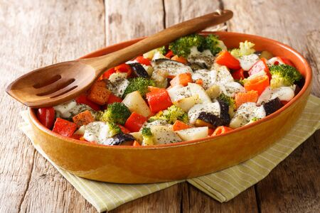 Homemade vegetable casserole with mozzarella cheese close-up in a baking dish on the table. horizontal
