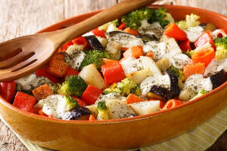 Healthy baked vegetables with mozzarella cheese close-up in a baking dish on the table. horizontal  Reklamní fotografie