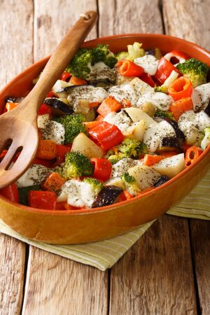 Hot healthy gratin of potatoes, carrots, eggplant, peppers, tomatoes and cheese close-up in a baking dish on the table. vertical
