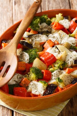 Fresh gratin of vegetables with cheese close-up in a baking dish on the table. vertical  Reklamní fotografie
