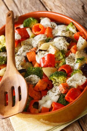 vegetarian vegetable casserole with cheese close-up in a baking dish on the table. vertical