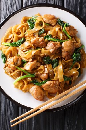 Pad See Ew – the popular Thai stir fried noodles closeup on the platr on the table. Vertical top view from above  Stockfoto