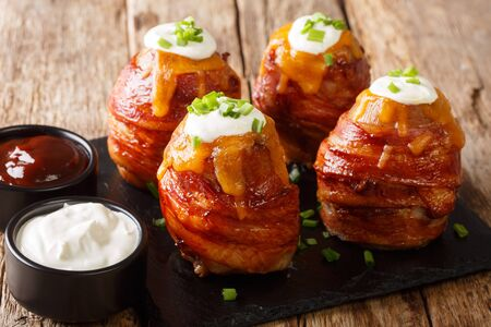Tasty hot appetizer volcano baked potatoes with bacon, cheese and onions close-up on the table. horizontal