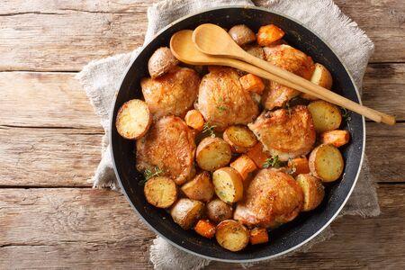 Gekochte Hähnchenschenkel mit Kartoffeln und Karotten Nahaufnahme in einer Pfanne auf dem Tisch. Horizontale Draufsicht von oben