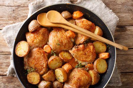Pollo al horno rústico con primer plano de verduras y hierbas en una sartén sobre la mesa. Receta francesa. Vista superior horizontal desde arriba