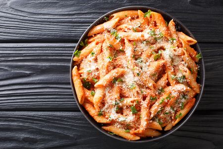 Penne alla Vodka is a classic Italian pasta dish made with penne in a creamy tomato and vodka sauce close-up in a plate on the table. Horizontal top view from above