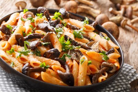 Serving penne pasta with roasted honey mushrooms and tomato sauce close-up in a plate on the table. horizontal