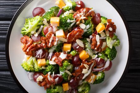 Fresh salad with broccoli, cheddar, grapes, bacon, almonds and onions with cream dressing close-up in a plate on the table. Horizontal top view from above