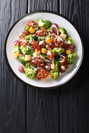 Broccoli, cheddar, grape, bacon, almond and onion salad recipe close-up in a plate on the table. Vertical top view from above Stock Photo