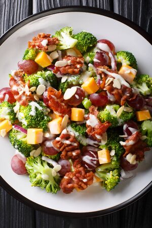 Tasty broccoli salad with cheddar cheese, grapes, bacon and onions close-up in a plate on the table. Vertical top view from above Stock Photo