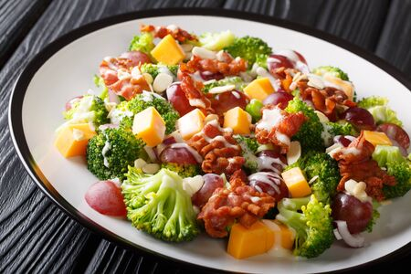 Serving of salad with broccoli, cheddar, grapes, bacon, almonds and onions close-up in a plate on the table. horizontal Stock Photo