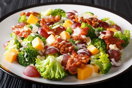 Fresh salad with broccoli, cheddar, grapes, bacon, almonds and onions with cream dressing close-up in a plate on the table. horizontal Stock Photo