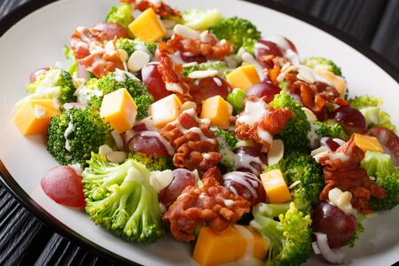 Broccoli salad with cheddar cheese, grapes, bacon, almonds and onions close-up in a plate on the table. horizontal