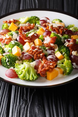 Broccoli, cheddar, grape, bacon, almond and onion salad recipe close-up in a plate on the table. Vertical Stock Photo