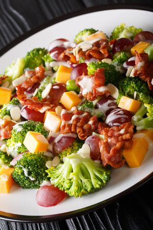 Tasty broccoli salad with cheddar cheese, grapes, bacon and onions close-up in a plate on the table. vertical