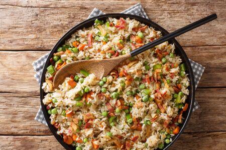 Arroz asiático con verduras de temporada y primer plano de tocino en un plato sobre la mesa.
