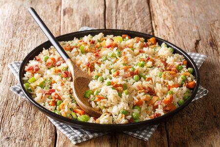 One pot of fried spicy rice with vegetables, herbs and bacon close-up in a plate on the table. Stock Photo