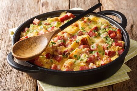 Tasty hot homemade strata with ham, onions, cheese and eggs close-up in a pan on the table.