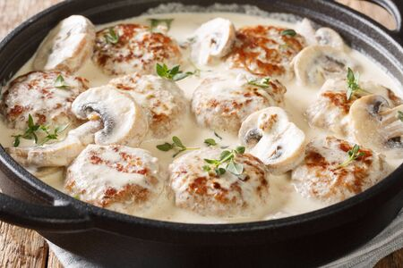 Hot meatballs with mushrooms served in creamy cheese sauce with thyme close-up in a pan on the table. horizontal Stock Photo