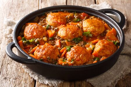 Spicy meatballs with lentil garnish in tomato sauce close-up in a pan on the table. horizontal