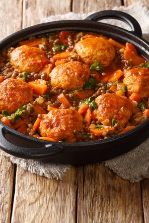 Delicious meatballs stewed with lentils and vegetables close-up in a pan on the table. vertical