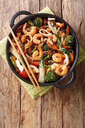 Gebratene Garnelen, Tintenfisch und Muscheln mit frischem Gemüse Nahaufnahme in einer Pfanne auf dem Tisch. Vertikale Draufsicht von oben