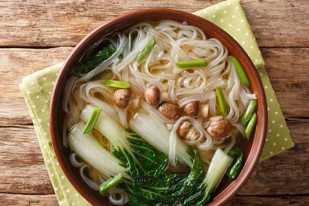 Diet Asian noodle soup with mushrooms, onions and bok choy close-up in a bowl on the table.