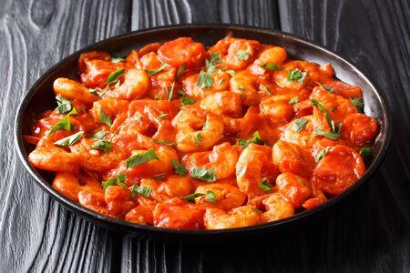 Gustosi gamberi fritti con aglio e spezie in salsa di pomodoro in primo piano in un piatto sul tavolo. orizzontale