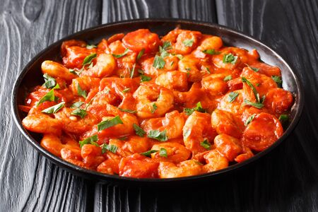 Smaczne krewetki smażone z czosnkiem i przyprawami w sosie pomidorowym z bliska na talerzu na stole. poziomy