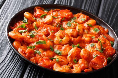 Knoblauchgarnelen serviert in würziger Tomatensauce Nahaufnahme in einem Teller auf dem Tisch. horizontal Standard-Bild