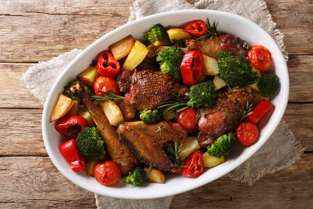 Kurczak balsamiczny z ziemniakami, brokułami, pomidorami i papryką z bliska w naczyniu do pieczenia na stole.