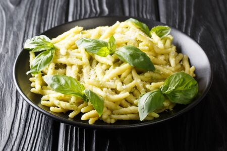 Ligurian trofie pasta cooked with basil pesto and parmesan cheese close-up in a plate on the table. Horizontal